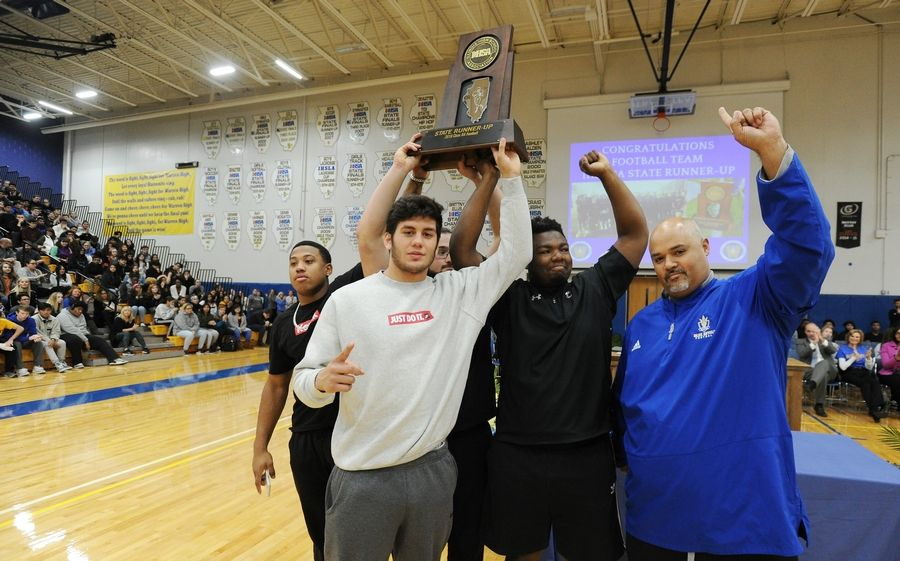 Team captains Willis Singleton, Christian Phillips, Matt Rich, Juan De La Cruz and head coach Bryan McNulty, right, hold up the second place trophy that capped the best season in school history, during a celebration Monday at the school's Almond Road campus.