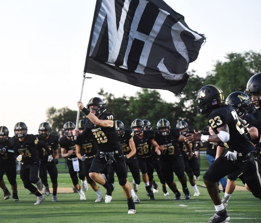 Grayslake North's Joe Swanson carries his team's flag prior to the start of a game against Antioch this past season. Football conferences will remain in tact in the future after IHSA member schools voted to rescind Proposal 23, it was announced on Wednesday.