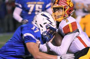 Batavia's Jack Meyers gets hit by Wheaton North's Xander Mueller during a game in 2018.