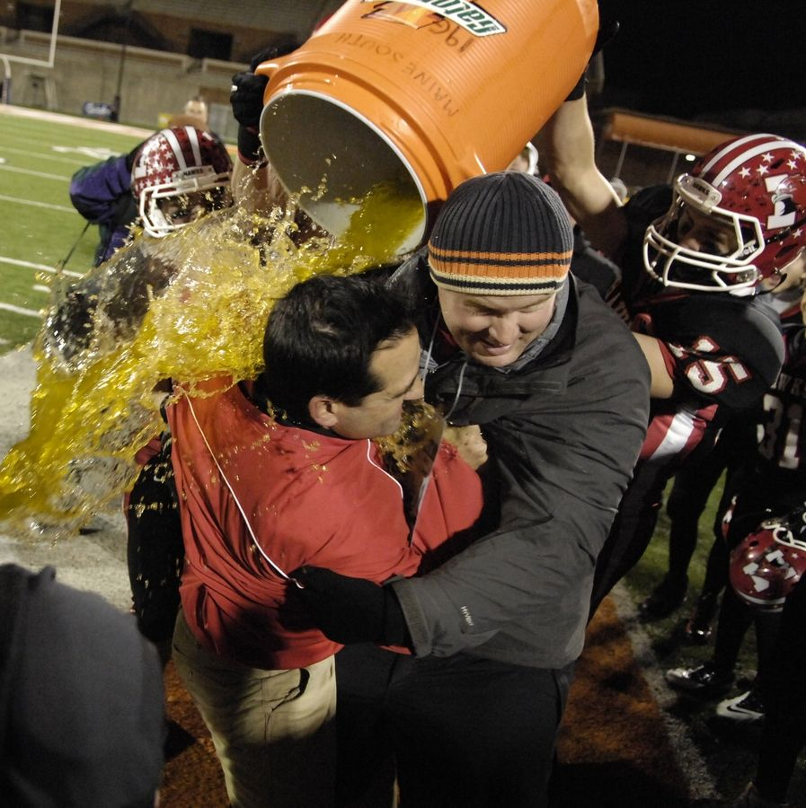 Maine South head coach David Inserra (in red) gets doused with Gatorade as the final seconds tick off the clock in the Hawks' win over Mt. Carmel during the 2010 Class 8A state final in Champaign.