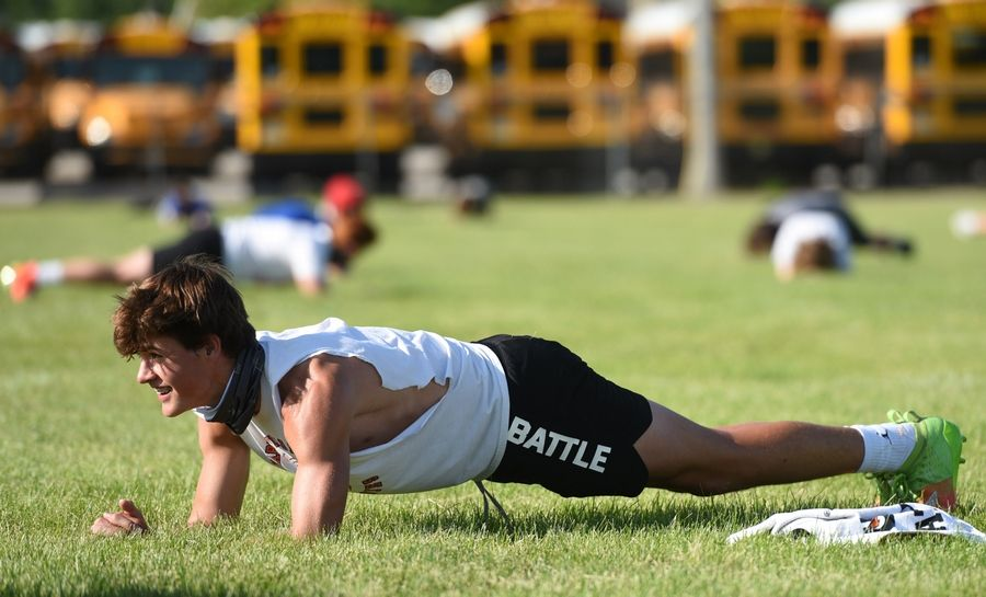 Naperville North sophomore football player Aiden Gray does planks during conditioning on Monday.