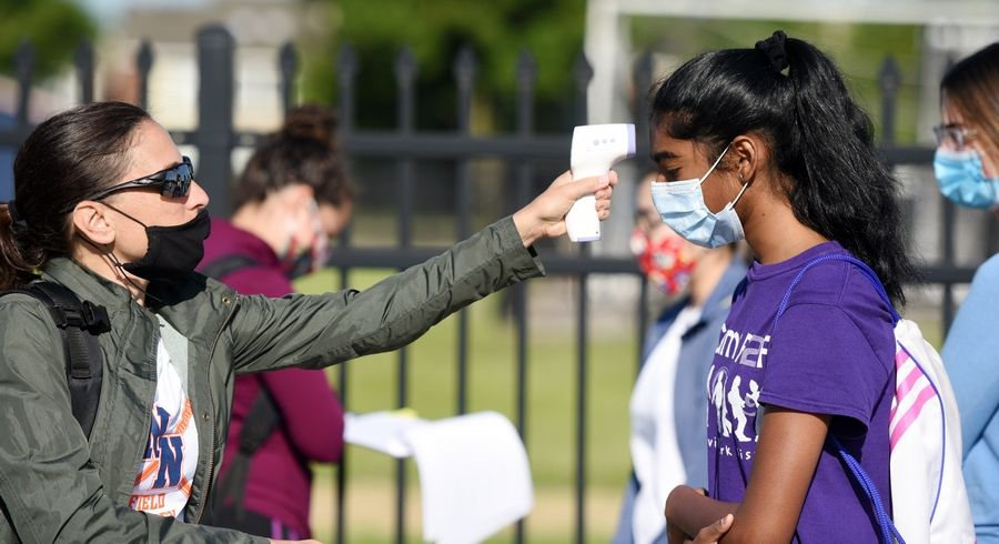 Naperville North field hockey coach Monica Lodge checks the temperature of sophomore lacrosse player Gautami Palthepu as athletes check in Monday for the school's first day of athletic conditioning.