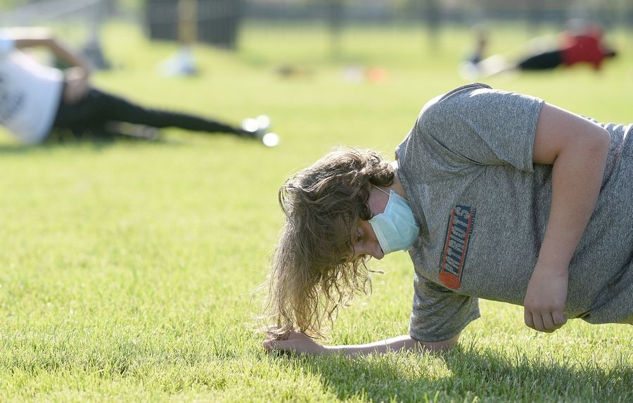 Naperville North freshman Josh Covick holds a side plank during the football team's conditioning drills.