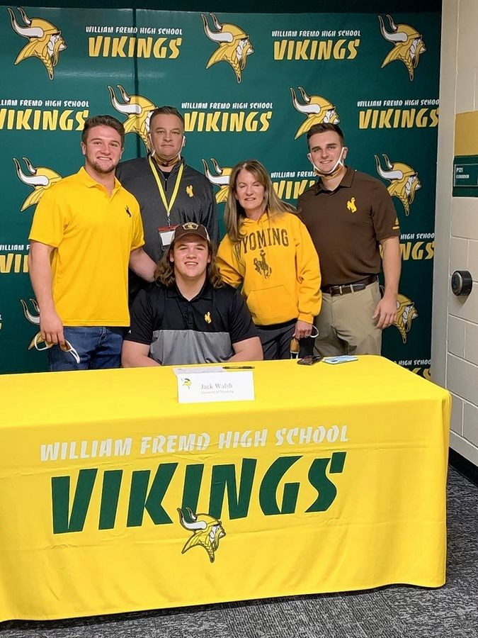 COURTESY OF DICK QUAGLIANOFremd's Jack Walsh, sitting, signed his National Letter of Intent on Wednesday to play football at the University of Wyoming. He was joined at the signing by his family, including brother Jimmy, from left, dad John, mom Kathy and brother Stephen.