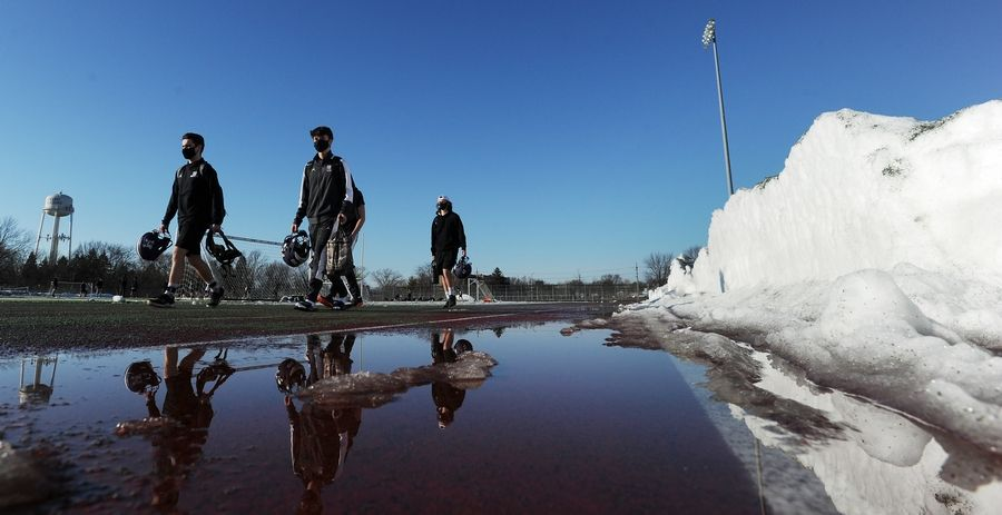 The Rolling Meadows football team hits the football field for their first practice as junior varsity and varsity football players walk past the snow cleared off the field.