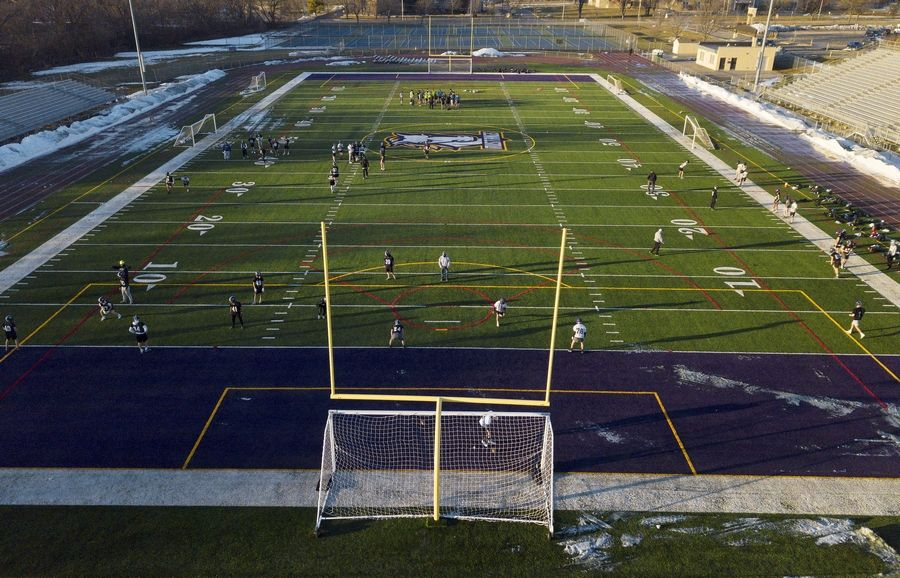 Coach Sam Baker and his Rolling Meadows football team hit the football field for their first practice surrounded by snow that was cleared off the field.