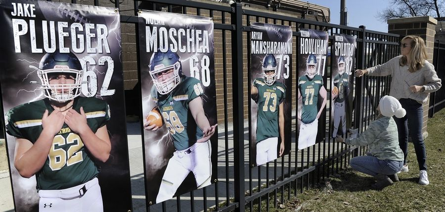 "Stevenson High School football supporters Vickie Loch and Pilar Norenberg (standing) hang team player banners along the fence line at Stevenson's stadium before the game, ""So excited"" Loch said as her son is playing on the varsity team Friday night against Waukegan."