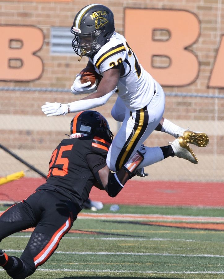 Metea Valley running back Kalen Riley Richardson is upended by DeKalb's Tyrell Donahue during their game Saturday afternoon at DeKalb High School.