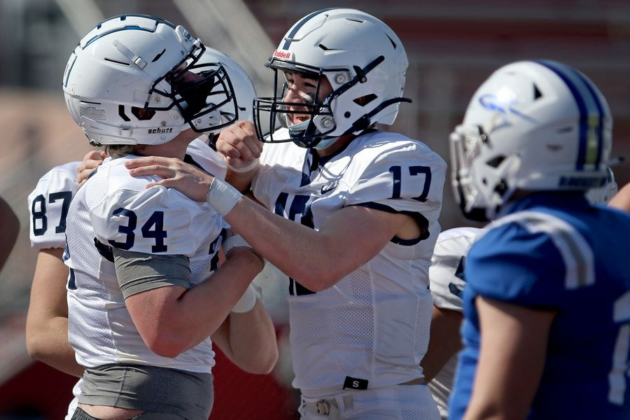 Cary-Grove quarterback Jameson Sheehan, center, congratulates teammate Nicholas Hissong, left, on his touchdown run against Burlington Central during their season opening football game at Huntley High School on Saturday, March 20, 2021 in Huntley.