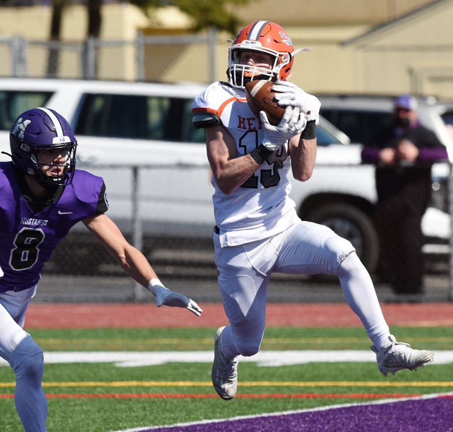 Hersey's Dylan Carlquist is ahead of Rolling Meadows' Daniel Sobkowicz as he catches a pass for a touchdown during the second quarter of last Saturday's game at Rolling Meadows. Hersey won, recording the 250th win in program history.