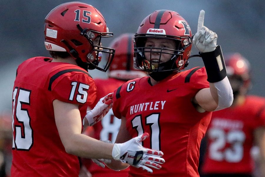 Huntley's Carter Knutsen, left, congratulates teammate Alex Janke as Janke holds his finger up in the air to celebrate his touchdown against Burlington Central during their football game at Huntley High School on Friday, March 26, 2021 in Huntley.