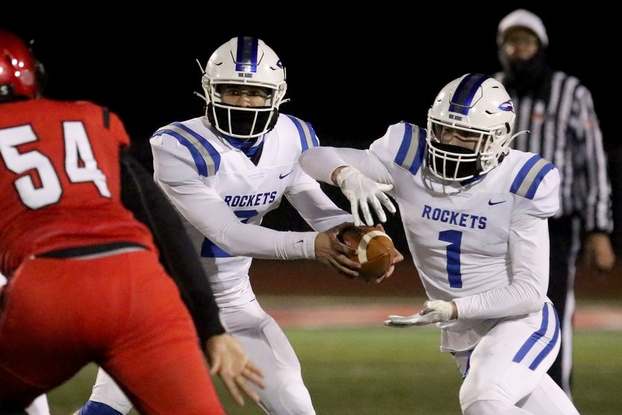 Burlington Central quarterback Mark Ganziano fakes a handoff to Gavin Sarvis during their football game against Huntley at Huntley High School on Friday, March 26, 2021 in Huntley.