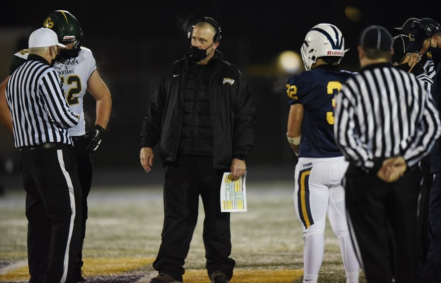 Glenbrook North head football coach Matt Purdy is at the center of the coin toss going into overtime during Friday's game against Glenbrook South. Glenbrook North won the game 21-14.