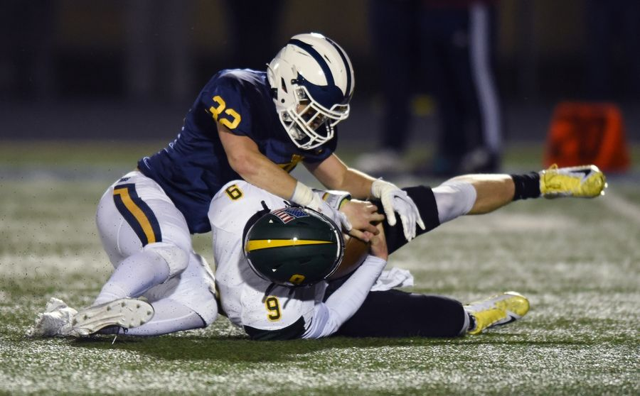 Glenbrook North quarterback Avery Burow, right, falls on a bad snap as Glenbrook South's Will Solis makes the tackle during Friday's game in Glenview.