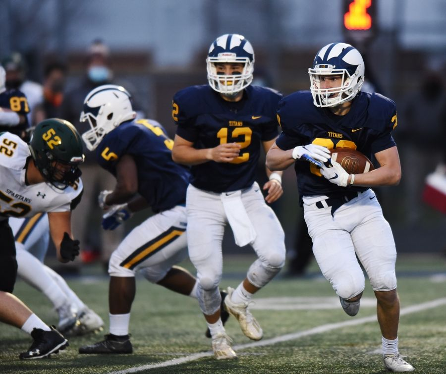 Glenbrook South's Thomas Gebien carries the ball after taking the handoff from quarterback Michael Bauer.