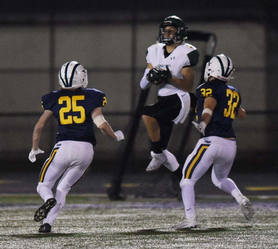 Glenbrook North's Zach Mendo catches a pass between Glenbrook South's Connor Weisensel, left, and Will Solis during Friday's game in Glenview.