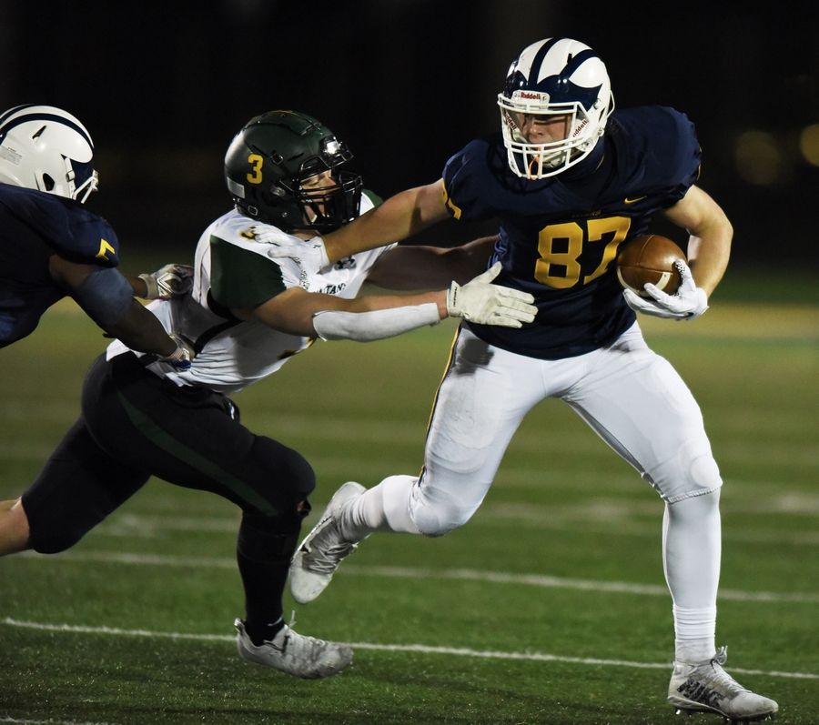 Glenbrook South's Jack Disano fends off Glenbrook North's JR Flood during Friday's game in Glenview
