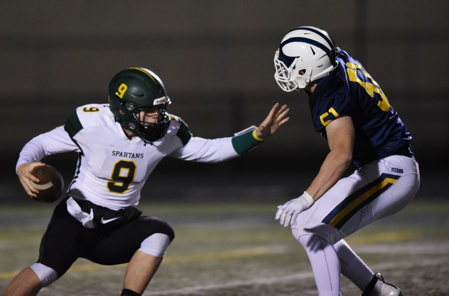 Glenbrook North quarterback Avery Burow tries to avoid a tackle by Glenbrook South's Jacque Gariepy during Friday's game in Glenview
