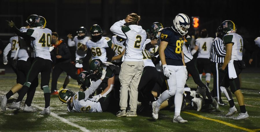 Glenbrook South's Jack Disano (87) walks away from celebrating Glenbrook North players following a 21-14 overtime loss in Glenview Friday.