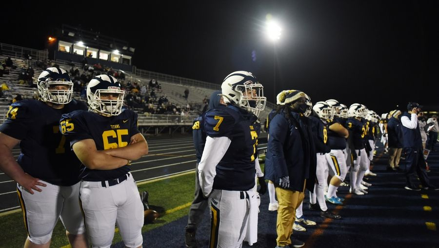 Glenbrook South players, including, from left, Jack Walsh, Jordan Buchta and Luca Pedrelli watch from the sideline as the Titans play the Glenbrook North Spartans in Glenview Friday.