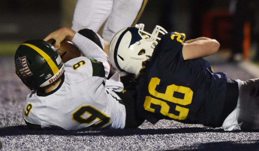 Glenbrook North quarterback Avery Burow, left, scores the Spartans' touchdown in overtime ahead of Glenbrook South's Michael Carney during Friday's game in Glenview.