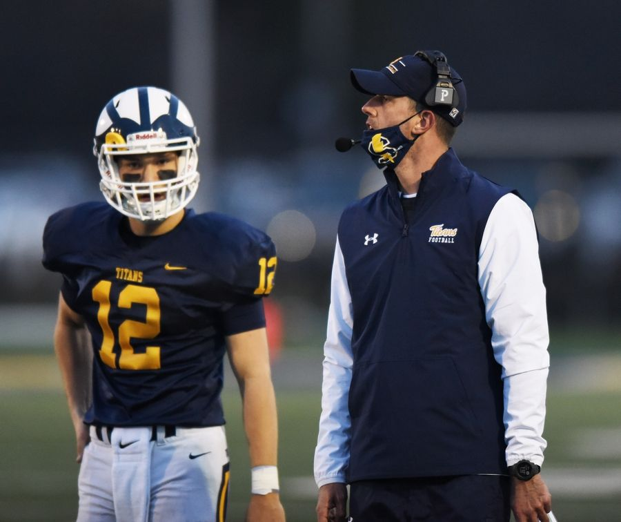 Glenbrook South football coach Dave Schoenwetter discusses the next play with quarterback Michael Bauer during Friday's game against Glenbrook North.