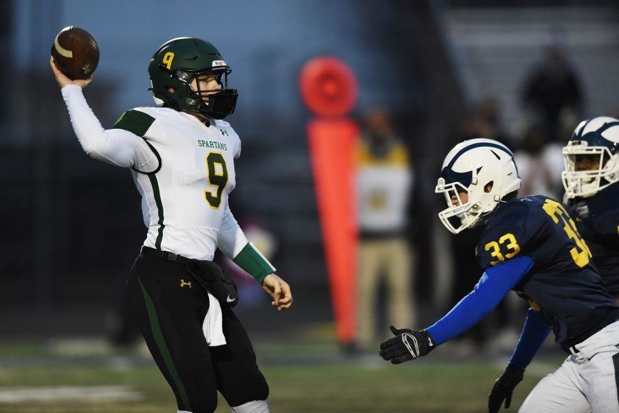 Glenbrook North quarterback Avery Burow throws a pass as Glenbrook South's Rory Tovcimak closes in Friday in Glenview.