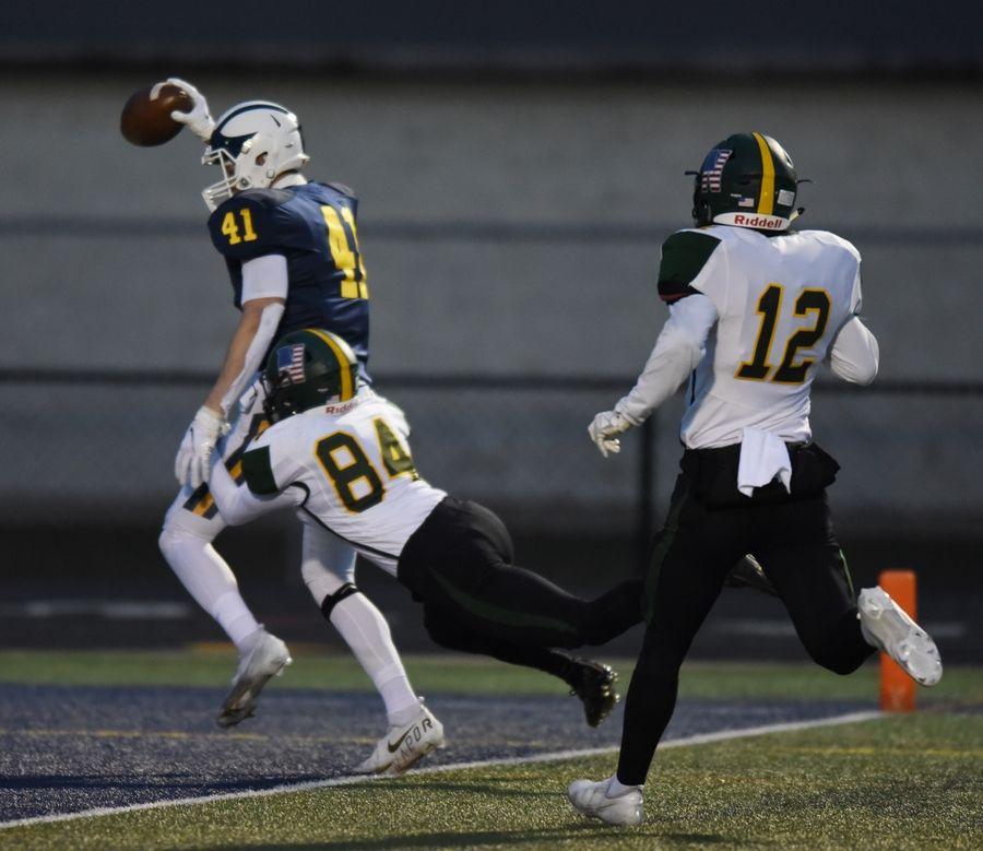Glenbrook South's Justin Leszynski scores a touchdown after catching a pass ahead of Glenbrook North's Nick Ullrich (84) and Murphy Mulvihill during Friday's game in Glenview.
