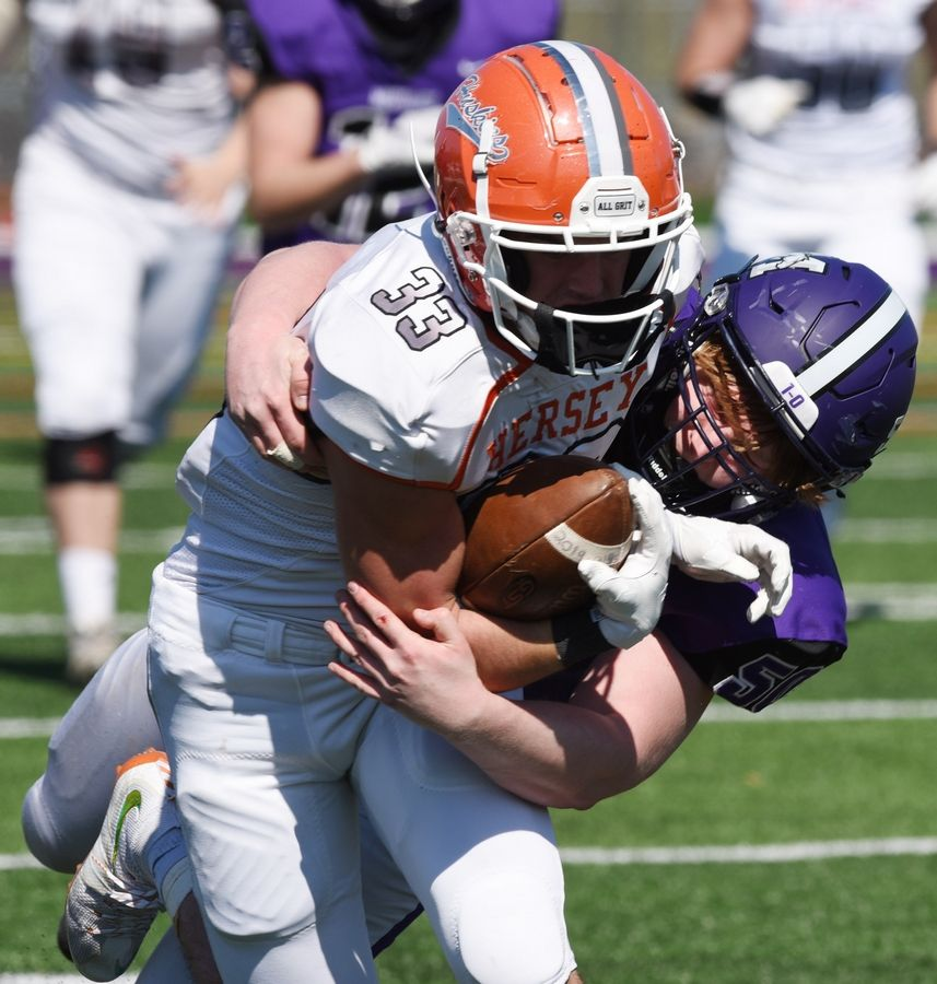 Hersey's Ben Clawson, left, gets tackled by Rolling Meadows' Nick Tannhauser during Week 1.