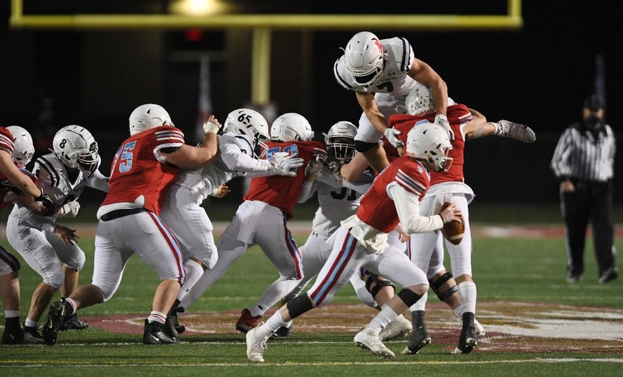 St. Viator's Daniel Niesman jumps over the line of scrimmage to try to tackle Marian Central's Brendan Hernon last week at Roosevelt University in Arlington Heights.