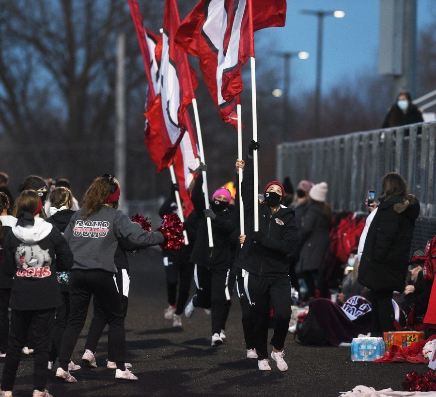 Grant High School cheerleaders run with the school's flags after the Bulldogs scored a touchdown against during a varsity football game on Thursday, Apr. 1 in Fox Lake.