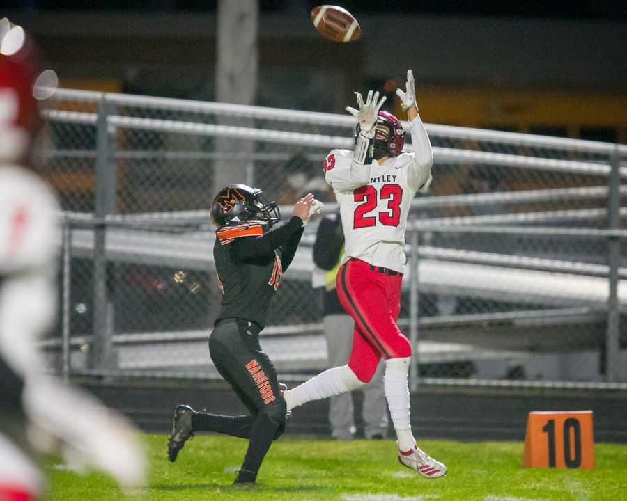 Huntley's Chase Jetel catches the ball over McHenry defensive back Brian Jordan Thursday at McHenry.