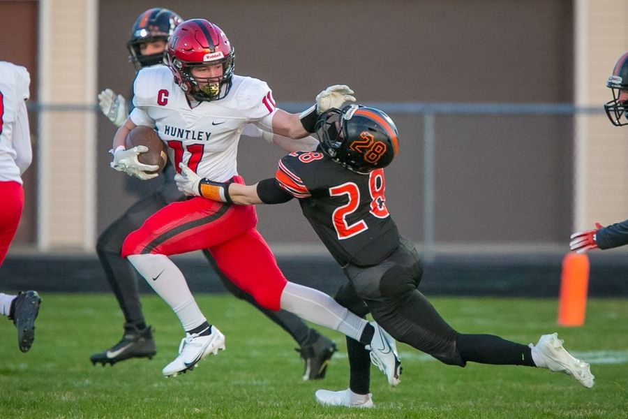Huntley's Alexander Janke (11) stiff arms McHenry's James LaRose (28) on a run on the initial kickoff in the first quarter of the game at McHenry High School East Campus on Thursday, April 1, 2021, in McHenry, Ill.