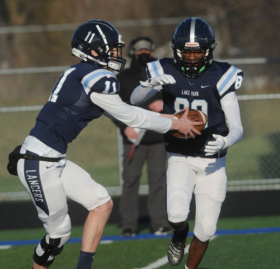 Lake Park's quarterback Brian Patton hands-off the ball to wide receiver Desmond Horton for short yardage in the varsity football matchup against Glenbard North at Lake Park High School on Friday.