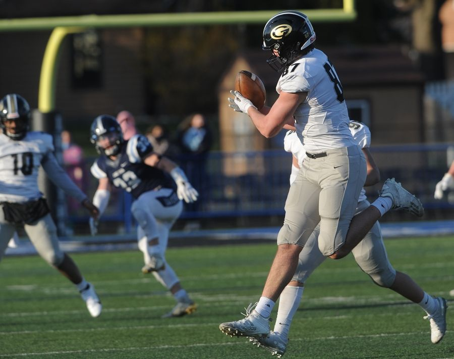 Glenbard North's Jake Cicero hauls in a second quarter pass play despite pressure from Lake Park's defense during the varsity football at Lake Park High School on Friday.