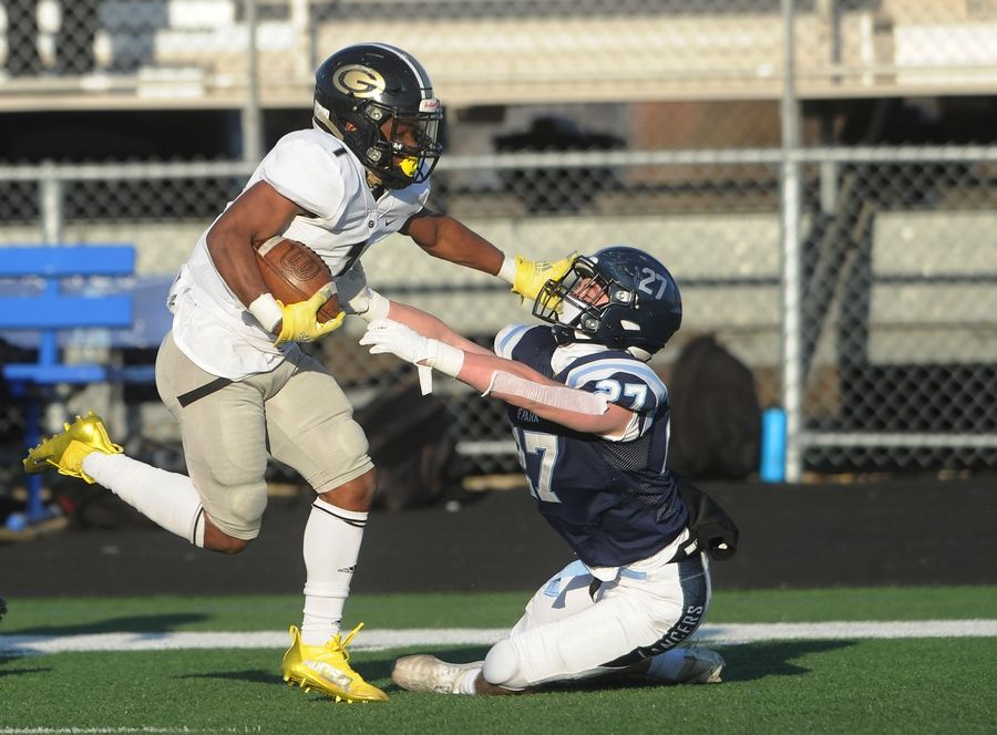 Glenbard North's running back Denhim Betney straight arms Lake Park's Ryan Prochaska and gains yardage in the second quarter of varsity football at Lake Park High School on Friday.