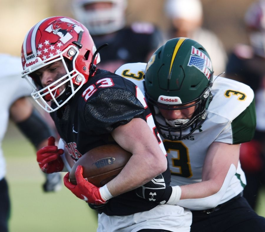 Maine South's Johnny Sassan, left, gets tackled by Glenbrook North's JR Flood during Saturday's game in Park Ridge.