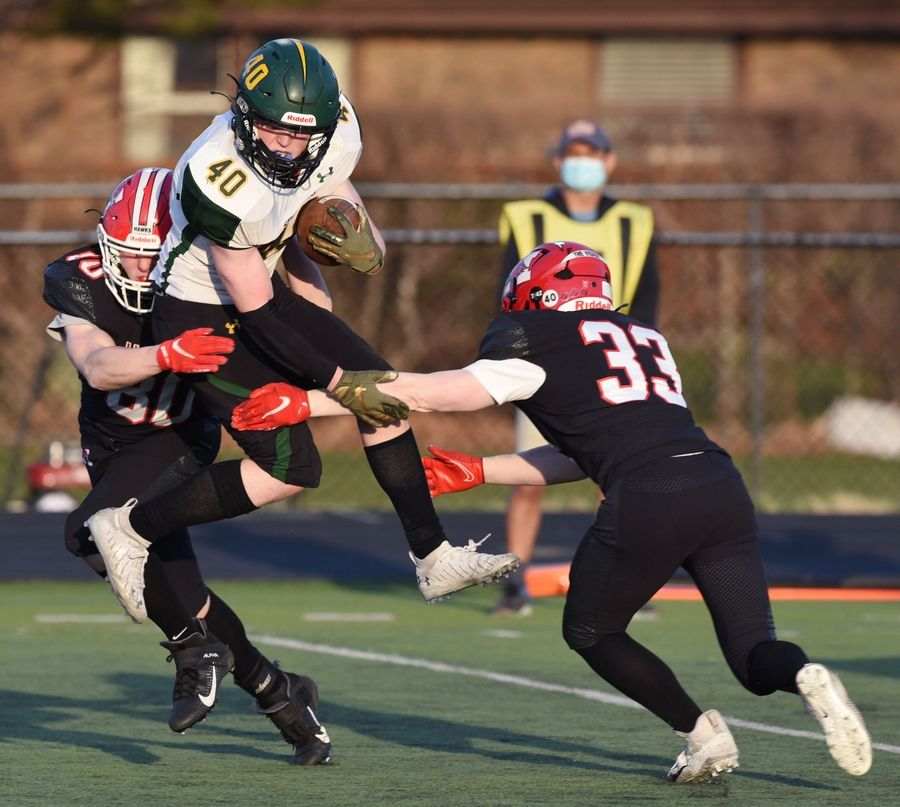 Glenbrook North's Quinn Clarke, middle, goes airborne as he is tackled by Maine South's Carter Collins, left, and Tommy Dillon during Saturday's game in Park Ridge.