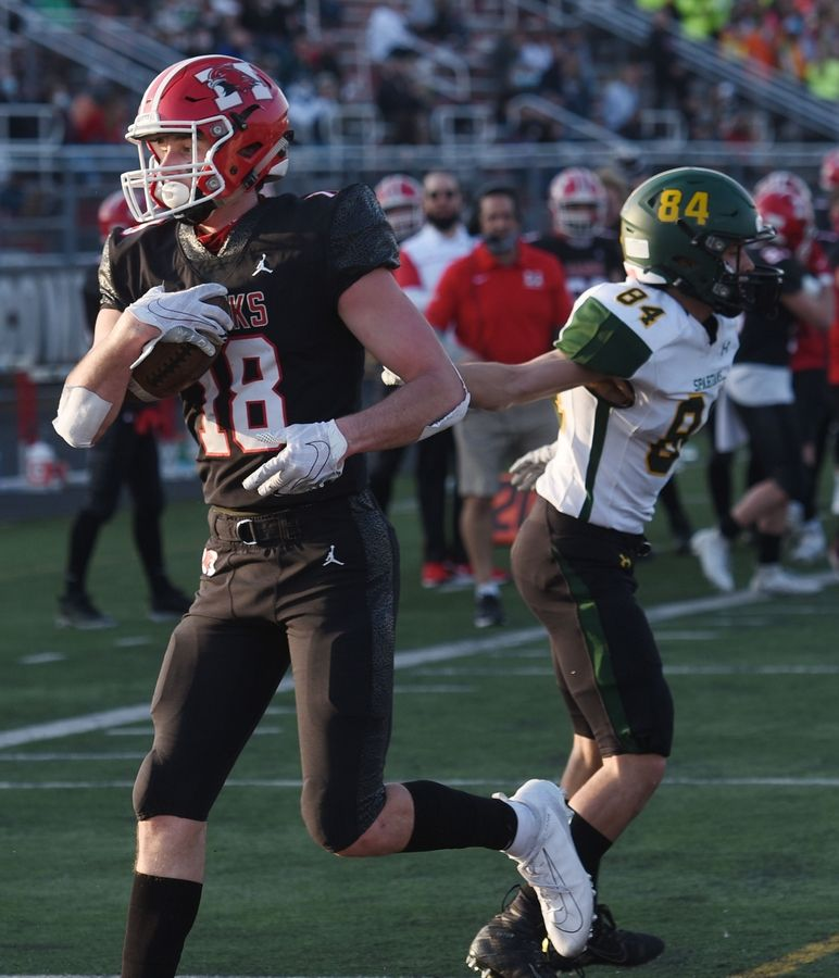Maine South's Chris Petrucci, left, runs the ball into the end zone after catching a touchdown pass against Glenbrook South defender Nick Ullrich during the second-quarter during Saturday's game in Park Ridge. Petrucci caught three passes for touchdowns during the quarter.