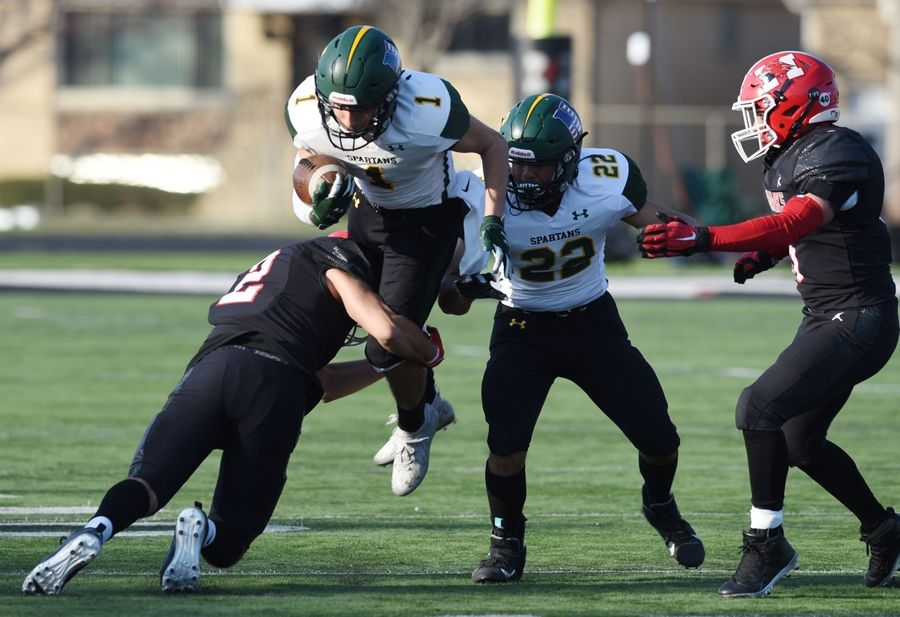 Glenbrook North's Zach Mendo (1) gets tackled by Maine South's Justine Marques during Saturday's game in Park Ridge.