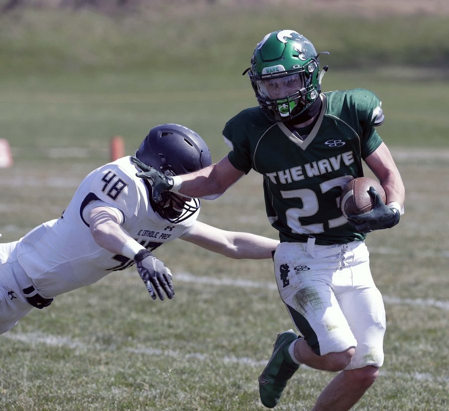 St. Edward's Joseph Sacco (23) moves out past IC Catholic's Connor McCoy (48) during football Saturday April 3, 2021 in Elgin.