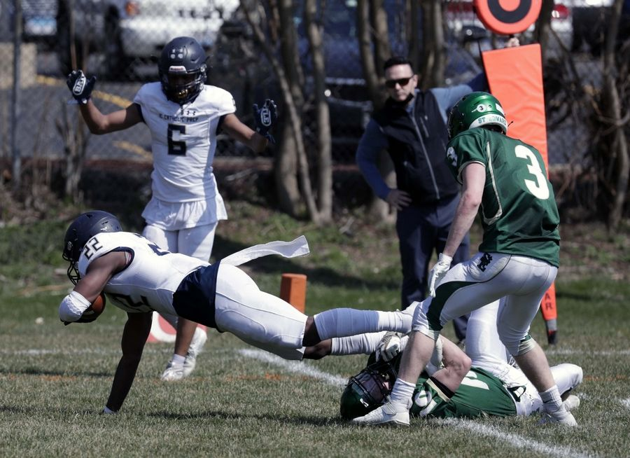 IC Catholic's Denzel Gibson (22) dives in for a touchdown as St. Edward's Liam Pomeroy (10) and Erik Hill (3) trie to stop him Saturday April 3, 2021 in Elgin.