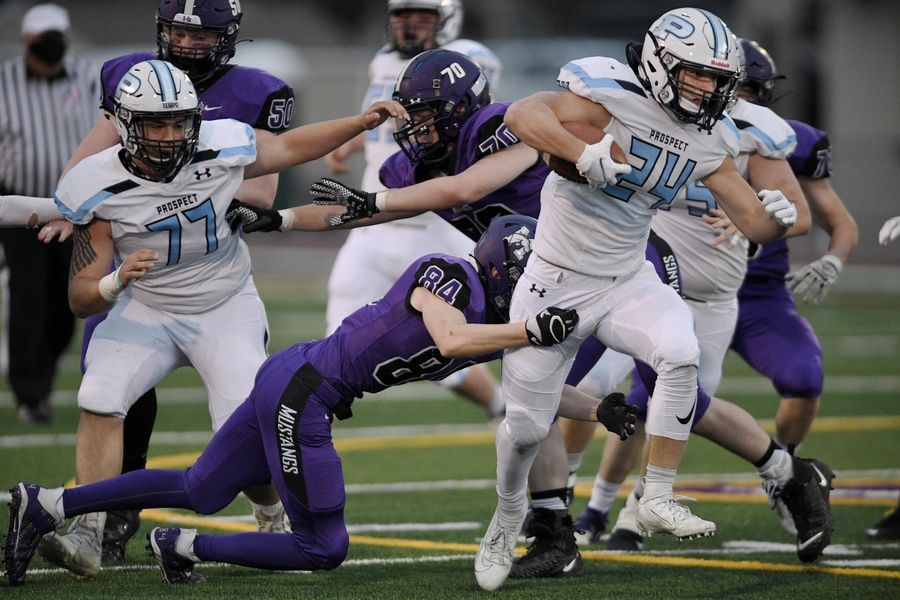 Prospect's Luke Zardzin escapes the grip of Rolling Meadows' Austin Schmidt on his way to a touchdown in a football game in Rolling Meadows Friday.