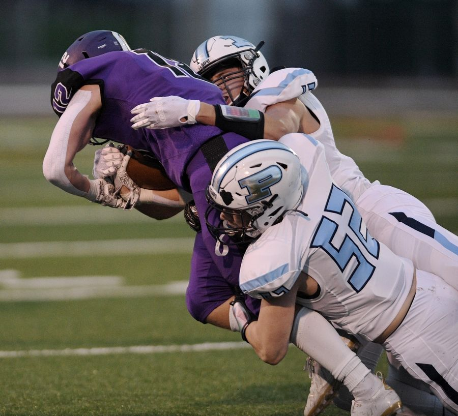 Prospect's Kris Bohnen and Gino Paredes stop Rolling Meadows' Charlie Schmidt in a football game in Rolling Meadows Friday.