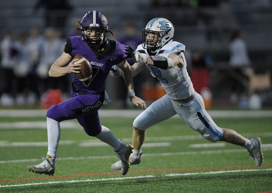 Rolling Meadows quarterback Michael Radon tries to escape the reach of Prospect's Decker Anderson in a football game in Rolling Meadows Friday.
