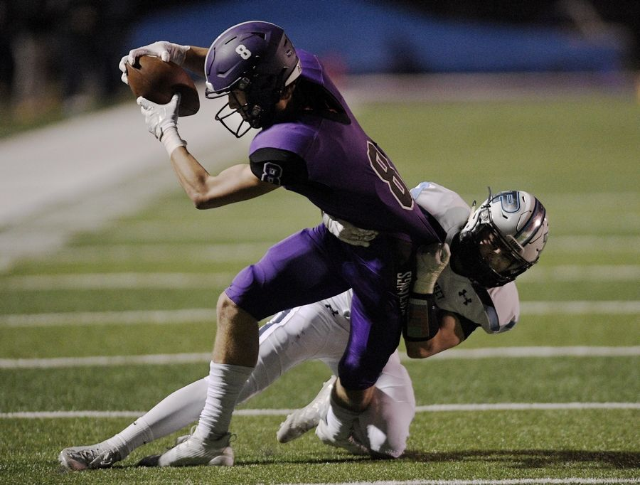 Rolling Meadows' Daniel Sobkowicz is brought down by Prospect's Nick Grassano after a catch in a football game in Rolling Meadows Friday.