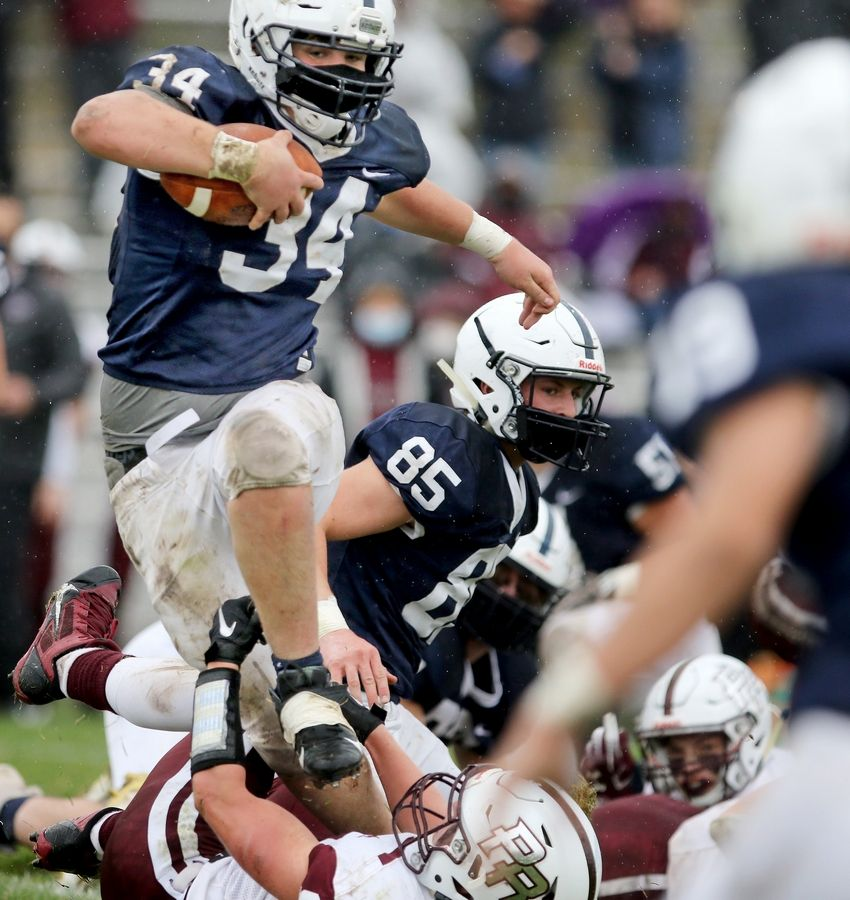 Cary-Grove's Nicholas Hissong jumps over Prairie Ridge's Matt Fryer on his way to a touchdown during their football game on Saturday, April 10, 2021 at Cary-Grove High School in Cary. Cary-Grove won 20-7.