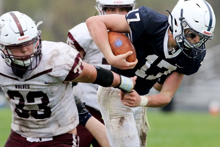 Cary-Grove quarterback Jameson Sheehan evades Prairie Ridge's Carter Evans, front, and Jack Schnoor, back during their football game on Saturday, April 10, 2021 at Cary-Grove High School in Cary. Cary-Grove won 20-7.