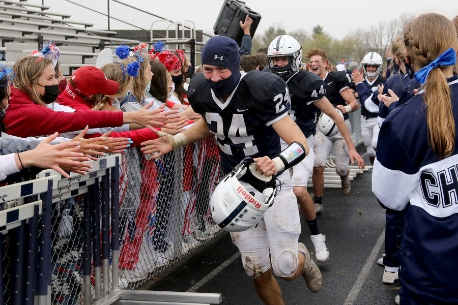 Cary-Grove's Anthony LaMantia runs through the gauntlet of high-fives from fans and clapping cheerleaders after beating Prairie Ridge during their football game on Saturday, April 10, 2021 at Cary-Grove High School in Cary. Cary-Grove won 20-7.