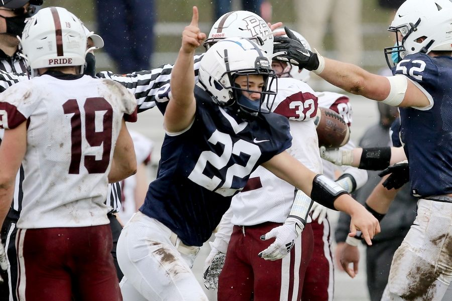 Cary-Grove's Toby Splitt runs from a pile of players celebrating a turnover from Prairie Ridge during their football game on Saturday, April 10, 2021 at Cary-Grove High School in Cary. Cary-Grove won 20-7.
